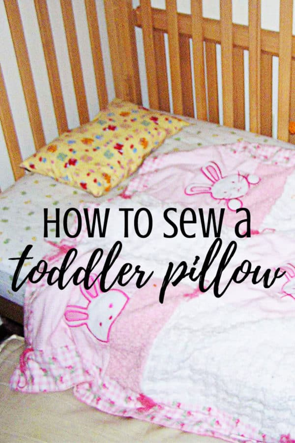 A baby bed with a blanket and pillow