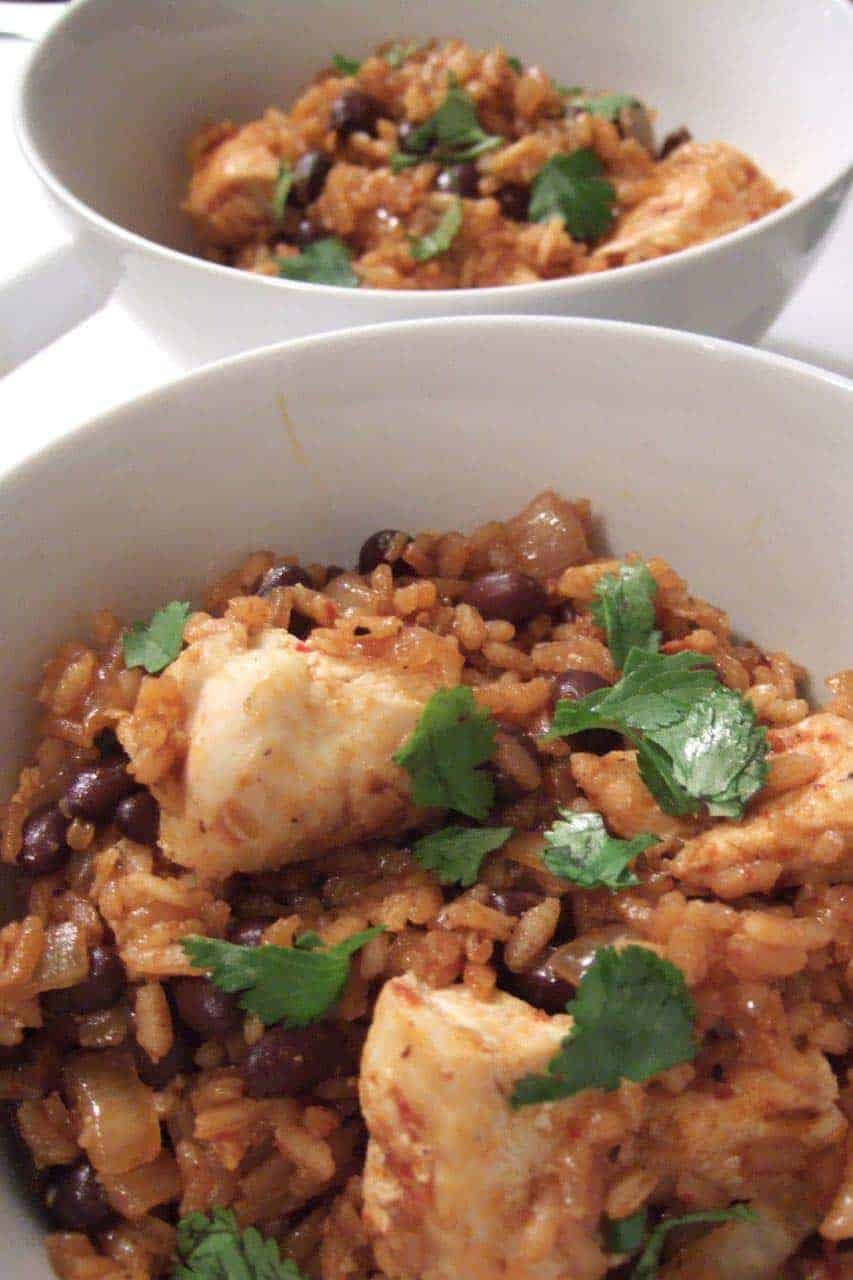 The best Cajun style red pinto beans and rice recipe - This simple, quick, and easy dinner is healthy for the budget because it's cheap! Can be vegetarian or vegan or you can add some meat. Great for lunch or supper. Spicy recipe that's amazing with some shredded cheese, sour cream, and cilantro on top.