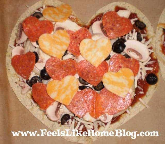 how to make simple and easy DIY individual heart shaped pizza - This quick and easy mini pizza uses tortillas instead of homemade dough so it comes together and cooks in under 15 minutes. Perfect activity for kids and families on Valentines Day. Fun food with heart pepperoni, sauce, and cheeses.