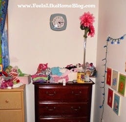 A bedroom with a bed and dresser in a room