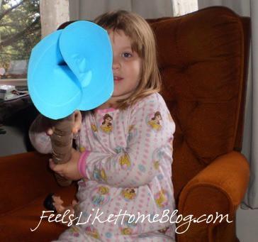 A little girl holding a her homemade fire hose