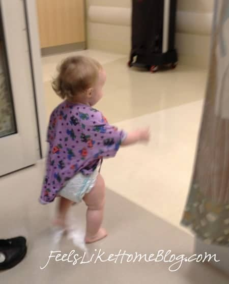 A little girl standing in front of a hospital room