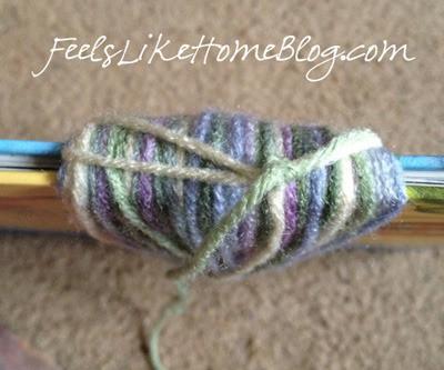 Tie a knot around the yarn