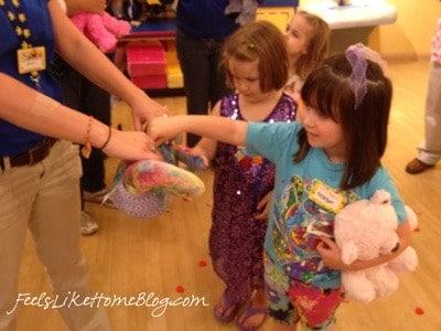 A little girl choosing a heart from Build A Bear Workshop