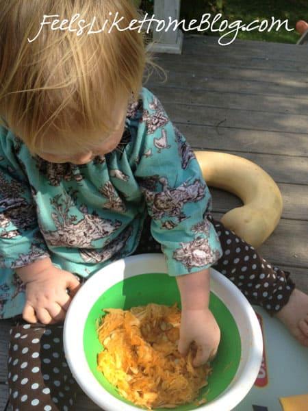 A little girl playing with pumpkin guts