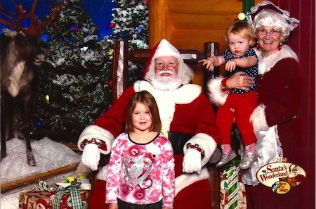 A little girl posing for a picture with Santa