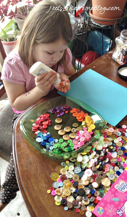 A little girl sitting at a table with a plate of buttons, all sorted by color