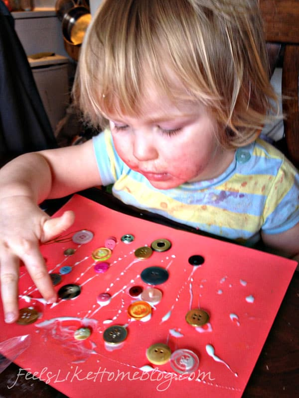 A small child gluing buttons on a piece of paper