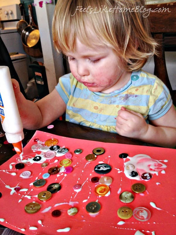 A small child putting glue on top of her buttons