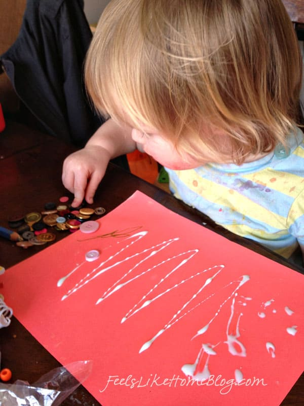 A little girl gluing buttons on a piece of paper