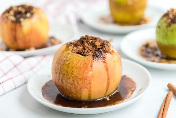 one baked stuffed apple with juice on a plate