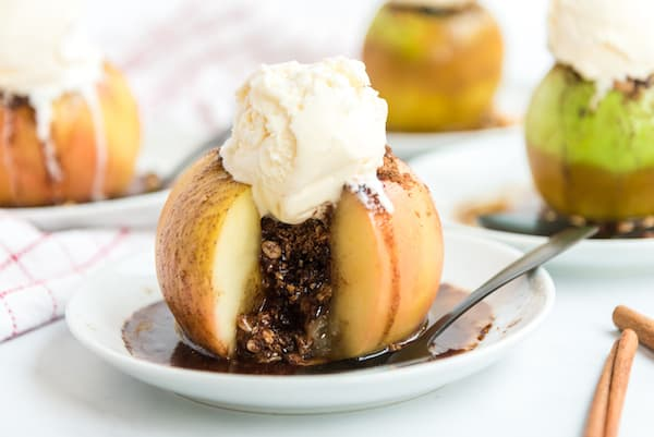 a baked apple with filling running out and a scoop of ice cream on top