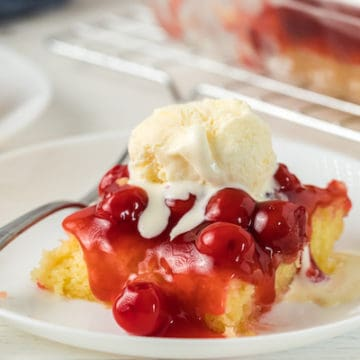 slice of gluten free cherry almond cake topped with ice cream