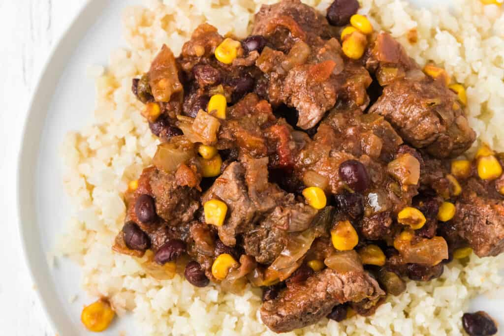 a close up of steak, corn, beans, and rice on a plate