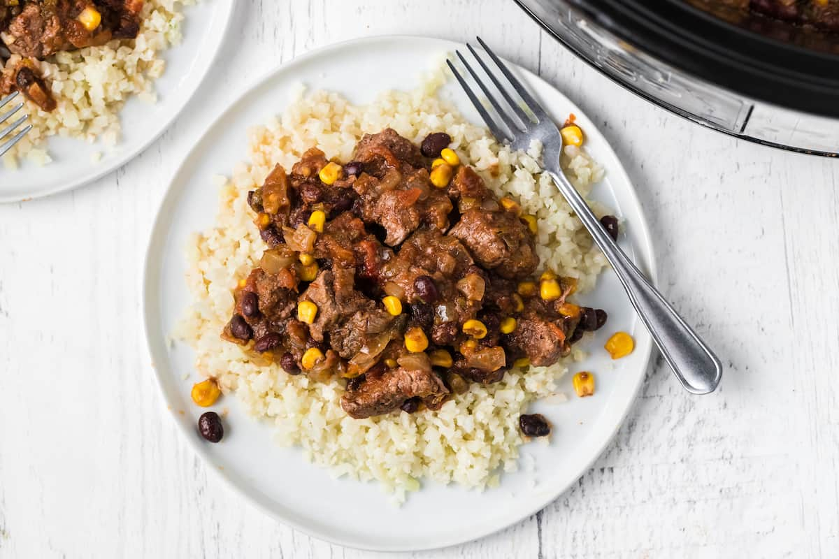 steak, beans, and corn on top of rice on a plate