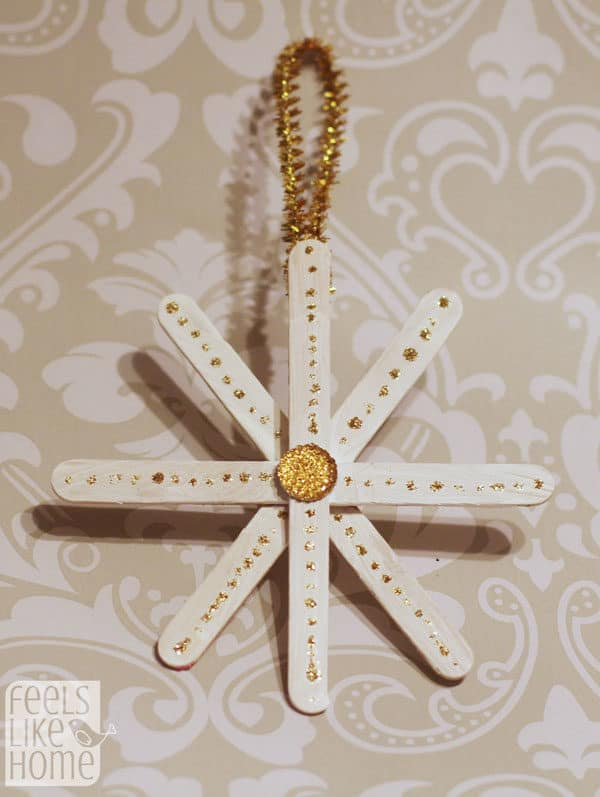 A gold snowflake made of popsicle sticks