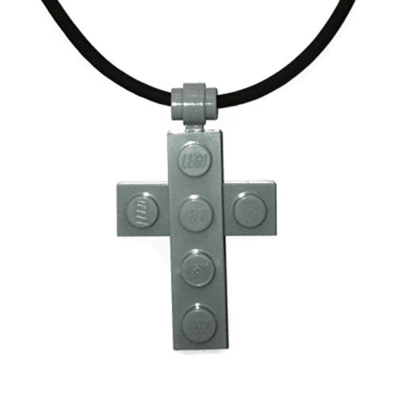 A close up of a Lego cross necklace