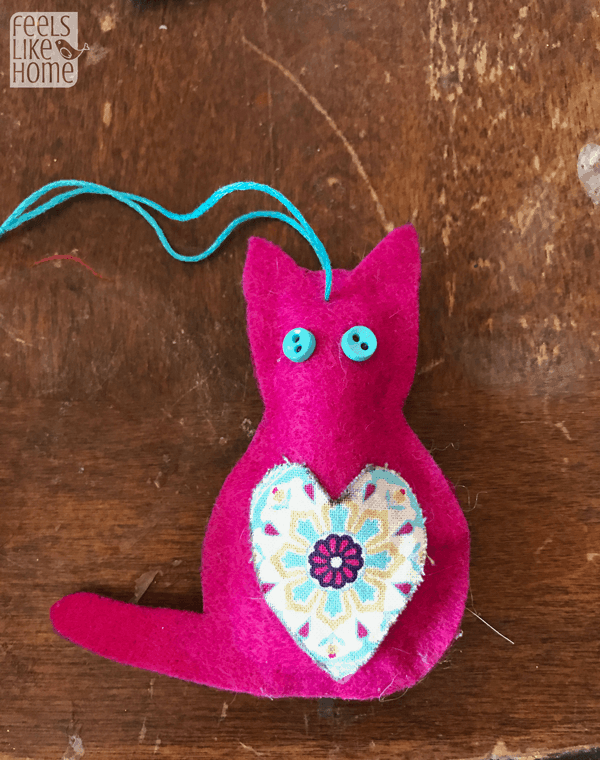 Glue buttons on the cat for eyes and thread a piece of string through both sides for a hanger