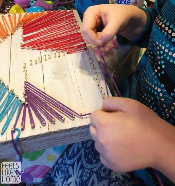 8 year old making DIY string art
