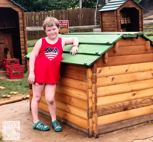 A girl standing in front of a house that she built