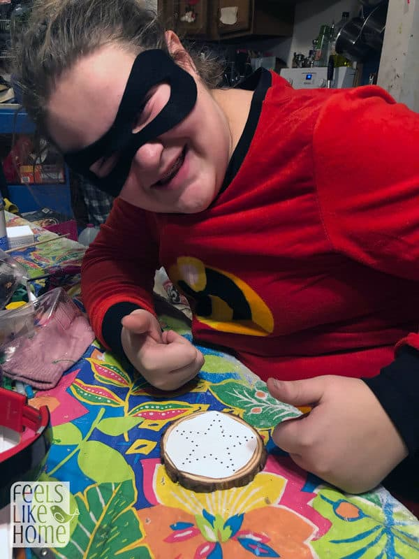 A tween girl in a superhero costume working on string art
