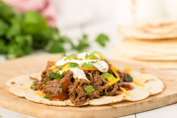 Easy Instant Pot recipe for the best shredded beef tacos - This simple and easy beef recipe uses homemade spicy enchilada sauce made on the stovetop to make a smothered beef that is juicy and delicious. Healthy, authentic beef tacos with all the toppings. Keto, paleo, and low carb. Can be gluten-free if you use corn tortillas.