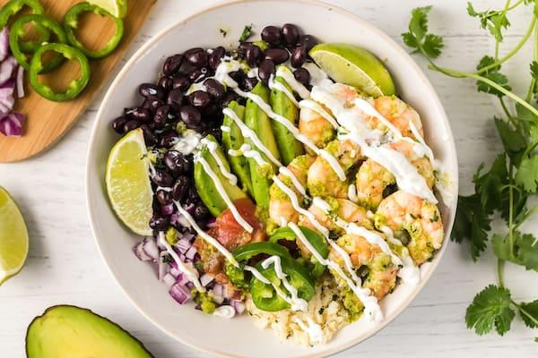 cilantro lime shrimp burrito bowl drizzled with sour cream