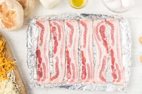 line a baking sheet with aluminum foil and arrange bacon in a single layer