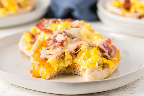 one bite missing from a mini breakfast pizza