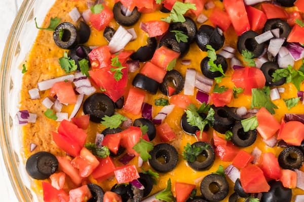 healthy taco dip with diced tomatoes, black olives, onion, and cilantro - up close